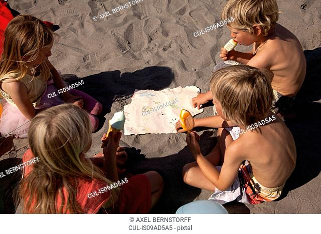 Four friends eating ice creams on beach, high angle, Wales, UK