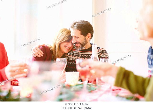 Couple hugging at family Christmas party