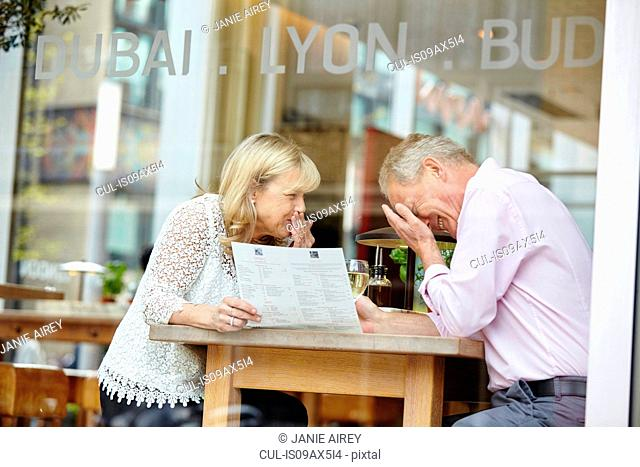 Mature dating couple giggling at restaurant table