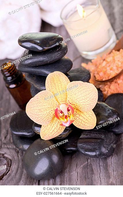 Spa with hot stones, bath salt, essential oil and towels close up