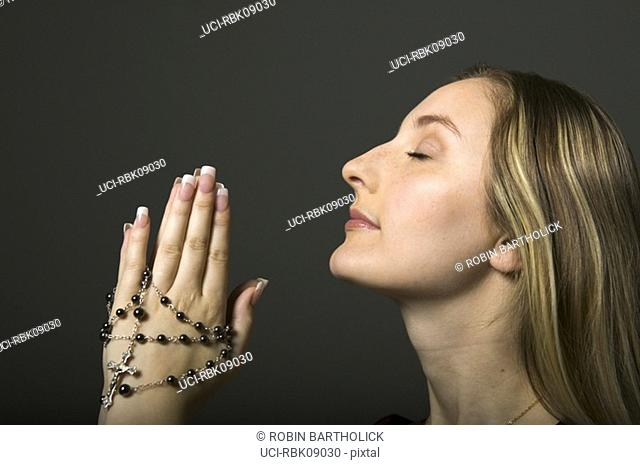 Young woman praying with rosary beads