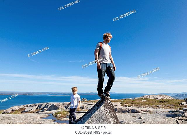 Boy and father looking out from top of rock formation over landscape, Aure, More og Romsdal, Norway