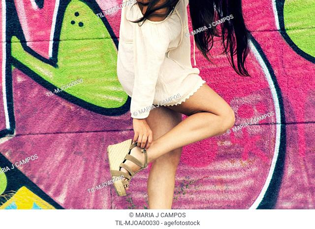 Headless shot of a woman with long brown hair and a baggy white shirt, fixing the strap of her sandal with colorful graffiti on the background