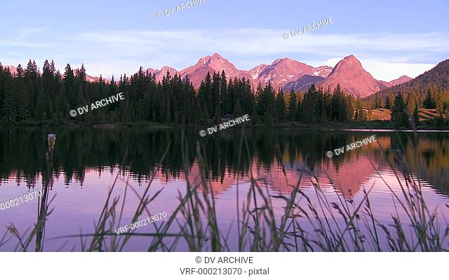 The Rocky Mountains are perfectly reflected in an alpine lake at sunset or dawn in this traveing shot