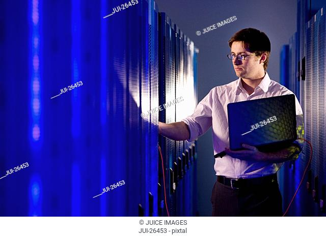 IT technician with laptop working in network server room