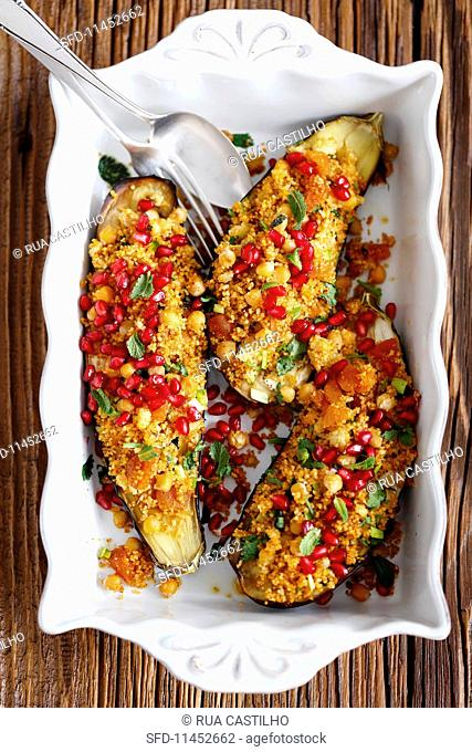 Aubergines filled with couscous, harissa, apricots, chickpeas and pomegranate seeds