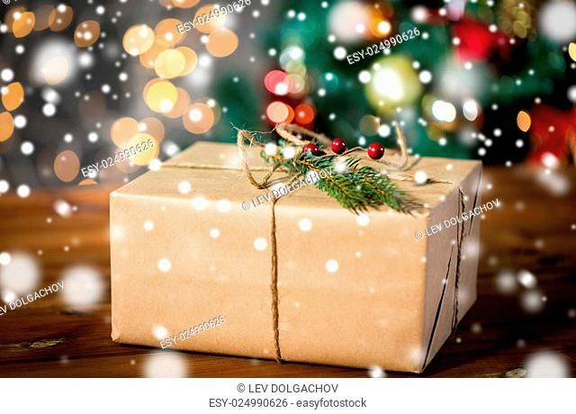 christmas, holidays, presents, new year and decor concept - close up of gift box wrapped into brown mail paper and decorated with fir brunch and rope bow over...