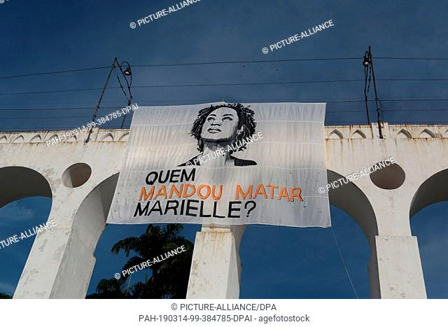 "14 March 2019, Brazil, Rio de Janeiro: """"Who commissioned the murder of Marielle?"""" says a poster at a rally one year after the murder of prominent city..."
