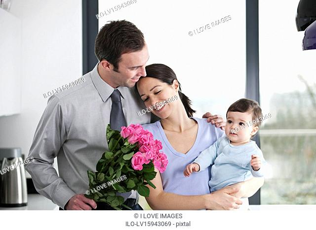 A man giving his partner a bunch of roses, woman holding their baby son