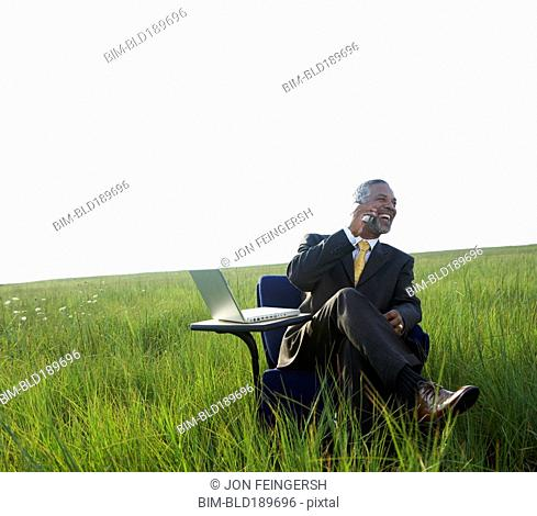 African businessman talking on cell phone in field
