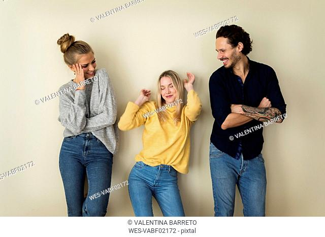 Three friends in front of a yellow wall, having fun