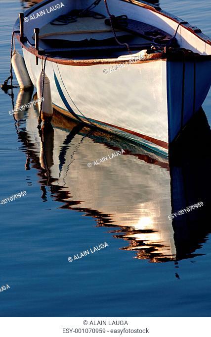 Morning light on a grey boat at anchor