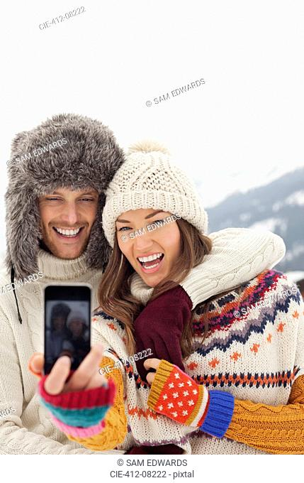 Enthusiastic couple taking self-portrait with camera phone