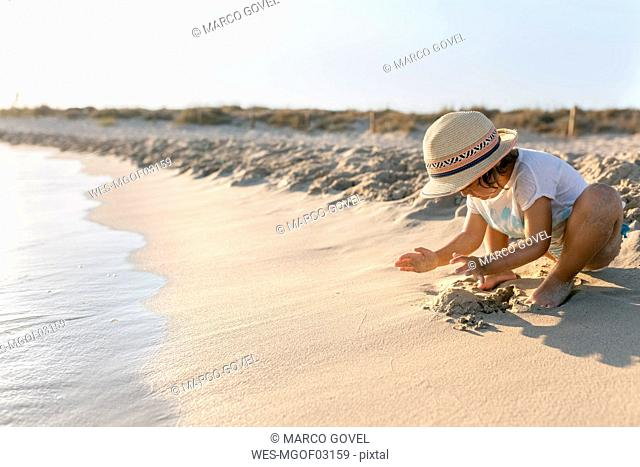 Spain, Menorca, little girl playing on the beach