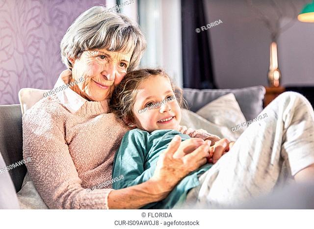 Girl on grandmothers lap on sofa
