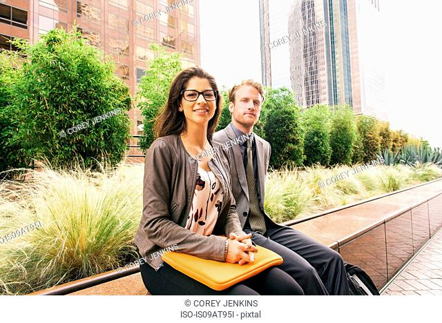 Businessman and woman sitting on wall with laptop in city