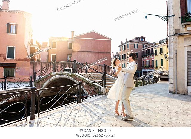 Italy, Venice, dancing bridal couple at sunrise
