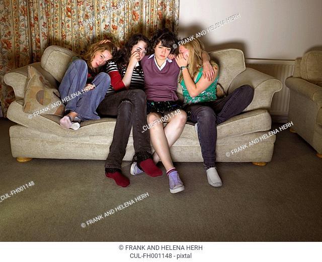 Women, sitting on sofa, looking sad