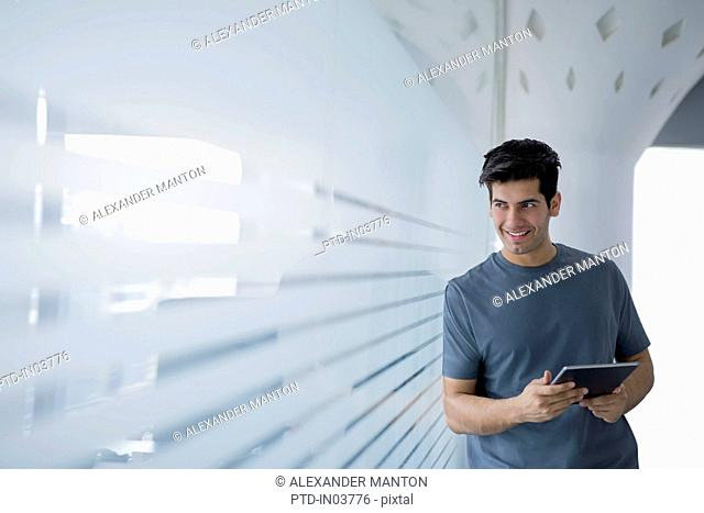 Young man in office leaning against glass wall using digital tablet