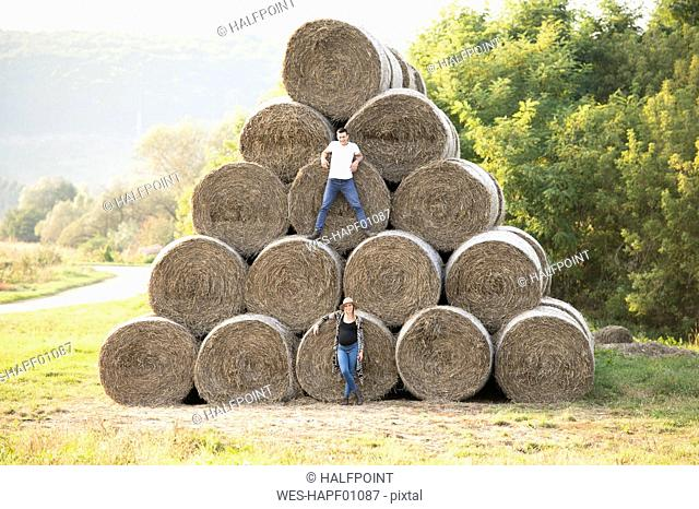 Expectant parents standing at bales of straw