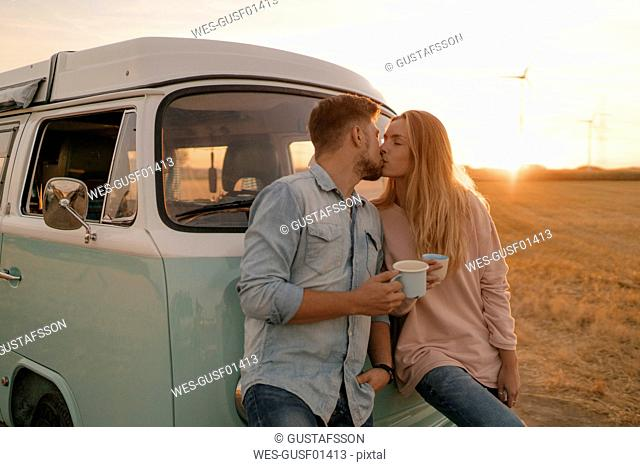 Young couple kissing at camper van in rural landscape