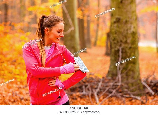 Rest and relax. Young attractive sporty girl with mobile phone smartphone on her arm with headphones listening music