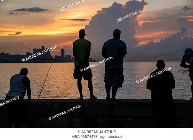 Angler as a silhouette at the Malecon in Havana, evening mood, orange and violet colours