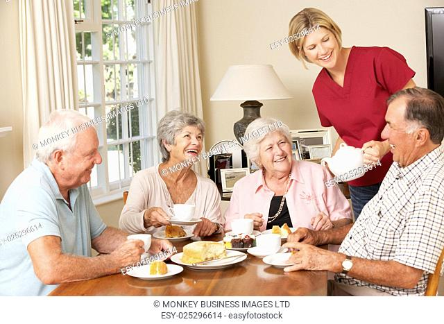 Group Of Senior Couples Enjoying Afternoon Tea Together At Home With Home Help
