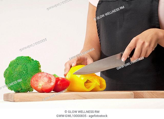 Woman cutting a yellow bell pepper and tomato