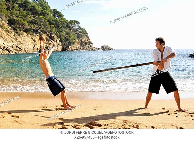 A teenager playing with his older brother at the beach
