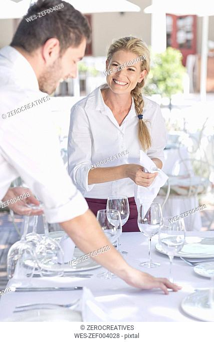 Waiters setting up an outdoor restaurant table