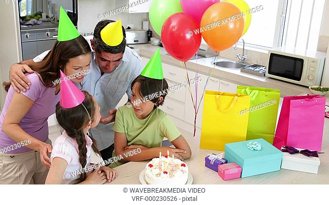 Happy family celebrating a birthday together at home in the kitchen