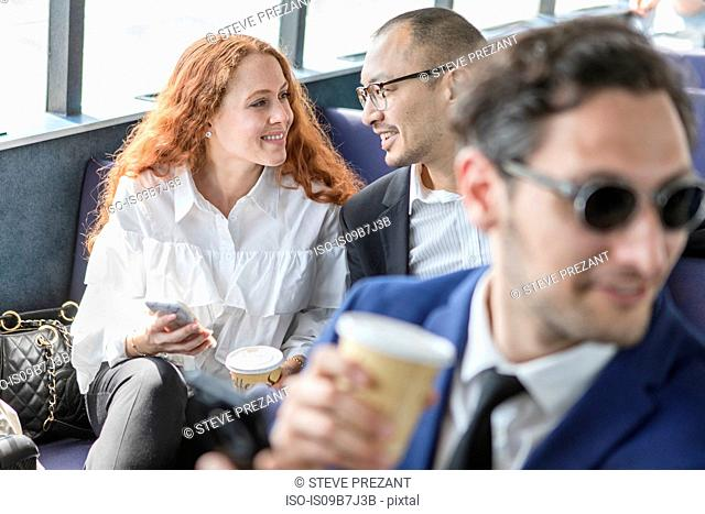 Businessman and woman chatting on passenger ferry