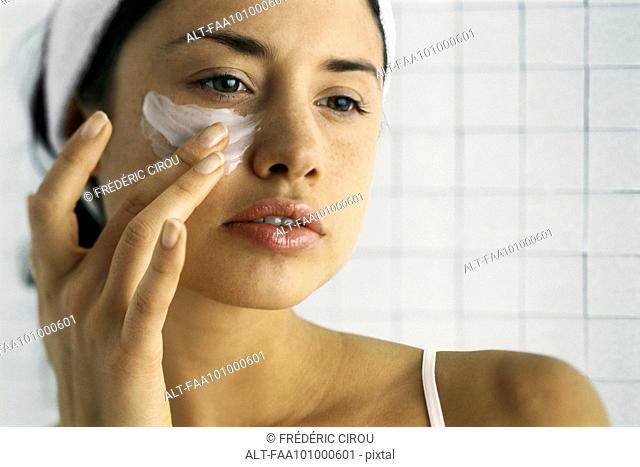 Young woman moisturizing face, close-up