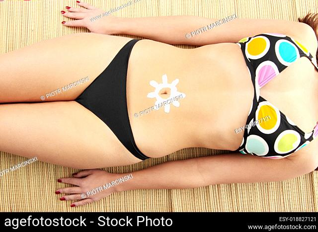 Young woman with sun-shaped sun cream