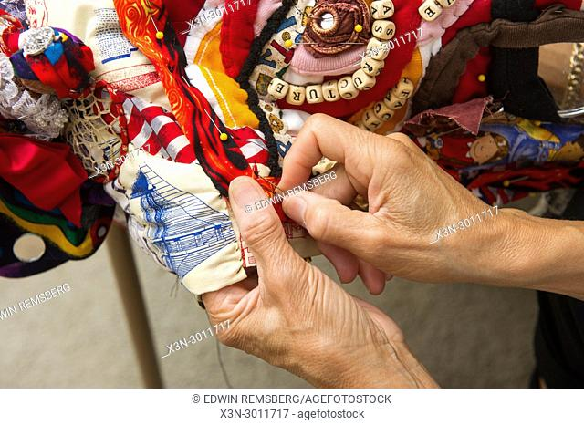 Women's hands placing pins in handmade quilt to prepare it for sewing, Severn, Maryland. USA