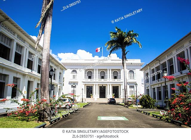 Gorgeous city hall with while column Louis Blanc with palm trees and park entrance in Fort de France, Martinique. The city hall looks like a white plantation...