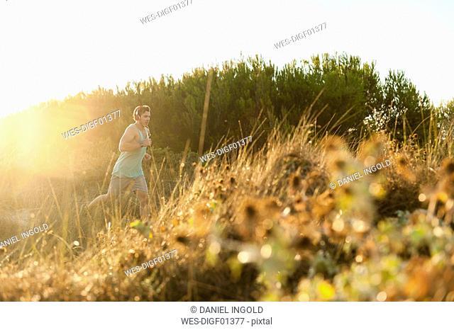 Spain, Mallorca, Jogger in dune at sunrise