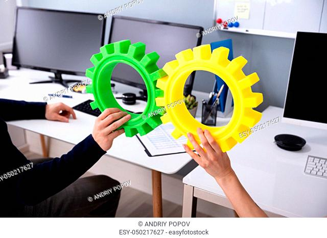 Two Businesspeople's Hand Joining Green And Yellow Gears In Front Of Black Screen Computer