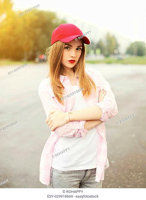Pretty young girl wearing a shirt and red cap outdoors