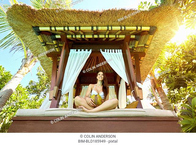 Pacific Islander woman sitting in cabana