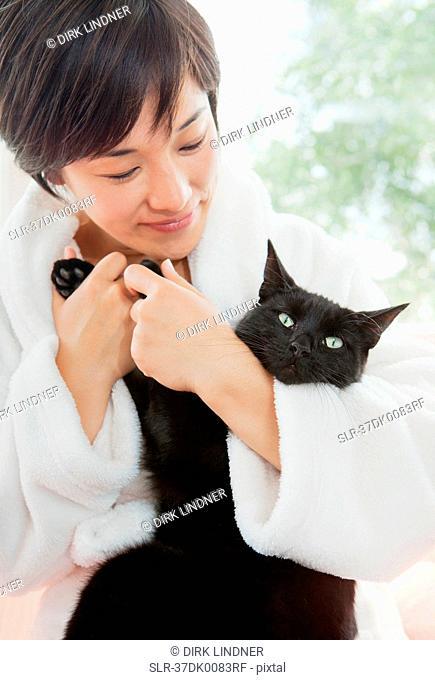 Woman in bathrobe holding cat