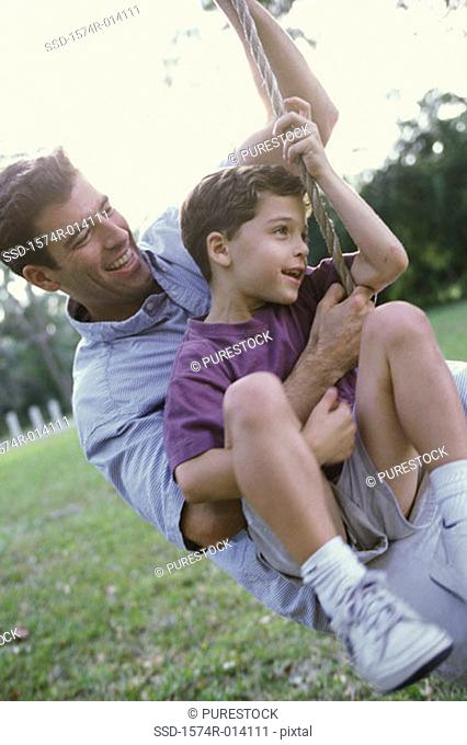 Close-up of a father and son swinging on a rope swing