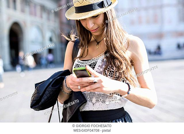 Italy, Bologna, young woman using smartphone