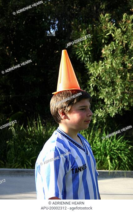 Young footballer in striped shirt, with cone on his head at practise