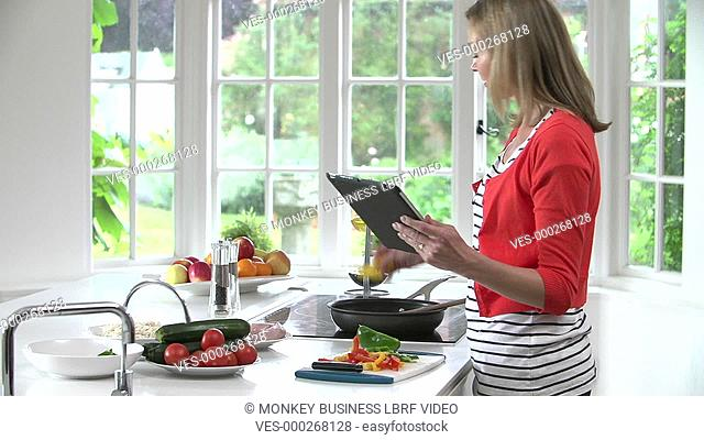 Woman checks recipe on digital tablet before adding peppers to frying pan.Shot on Sony FS700 in PAL format at a frame rate of 25fps