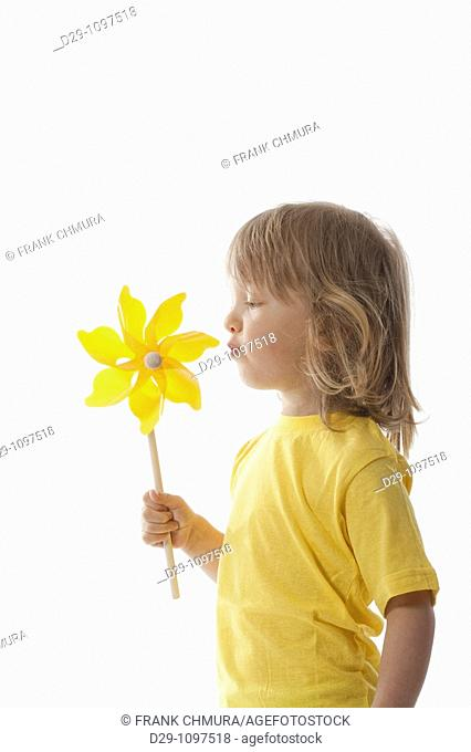 studio shot of a boy playing with pinwheel - isolated on white