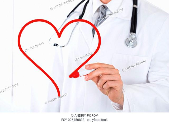 Close-up Of Doctor Hand Drawing A Heart Symbol With Red Marker