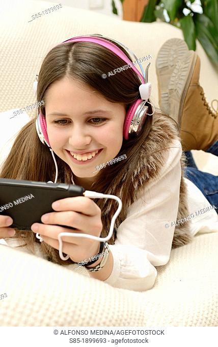 Smailing girl stretched on a couch and listening to music with your cell phone