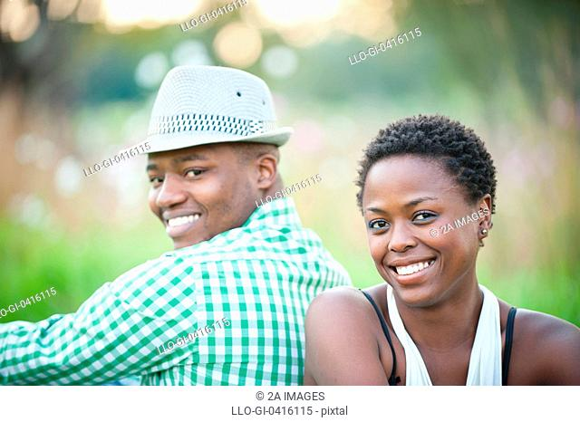 Portrait of young couple sitting back to back in park, Johannesburg, South Africa